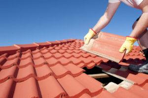 Afbeelding van man die dakpannen legt op dak