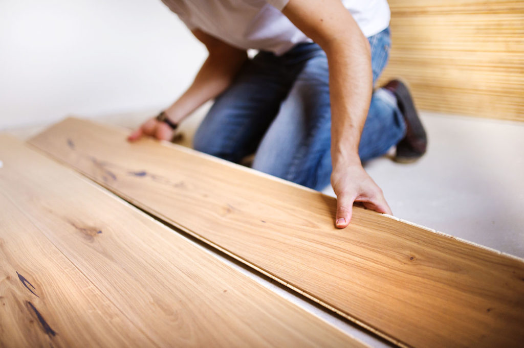 Een man plaats vloerisolatie en een houten vloer.