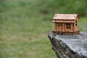 afbeelding van een miniatuur huis op fundamenten van een rots.