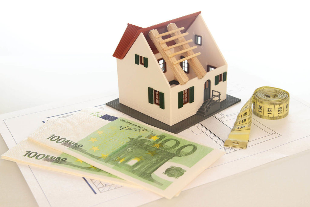 Afbeelding van een modelhuis en bankbiljetten die premies voorstellen.